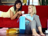 Two female friends with shopping bags sitting on the sofa NTSC Stock Footage