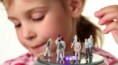 Girl holds toy figurines of woman, on toy podium stay toy figurines Stock Footage