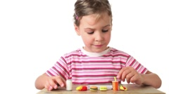 Girl puts on tray artificial food one by one Stock Footage