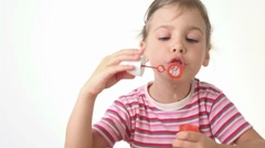 Girl blows soap bubbles and tries to catch them by stick Stock Footage