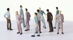 Several painted toy men stand and drop shadows - stock footage