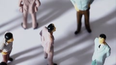 Few painted toy men stand and drop shadows - stock footage