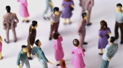 Some painted toy men and women stand in a jumble Stock Footage