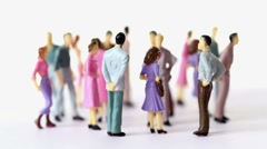 Group of painted toy men and women stand pell-mell Stock Footage