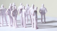 Group of little unpainted toy humans stand and drop shadows Stock Footage