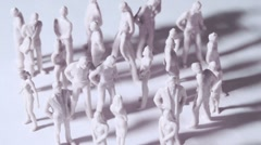 Group of little unpainted toy men and women stand and drop shadows - stock footage
