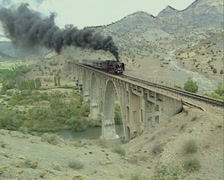 Steam train going over bridge approaching camera Stock Footage