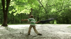 Boy circling, wind raises fluff from the ground in grove Stock Footage