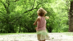Girl runs away across forest meadow all strewn fluff Stock Footage