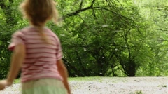 Girl hopping and runs away across meadow all strewn fluff, then she stops and Stock Footage