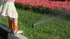Girl sits on border and touch stream of water pours on flowerbed Stock Footage