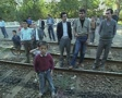 Children and men standing on train tracks looking at camera Footage