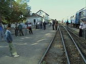 Pan across from station platform to train and people Stock Footage