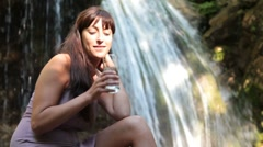 Young woman drinking a glass of mineral water Stock Footage