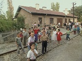Little children standing at train station and waving at camera Stock Footage