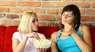 Two happy female friends eating popcorn and watching tv Stock Footage