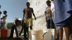 People get water from a well following a massive earthquake in Haiti. Stock Footage
