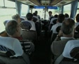 Tour group on travelling coach listening to tour guide Footage