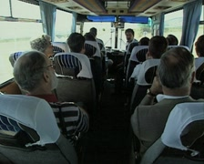 Tour group on travelling coach listening to tour guide Stock Footage