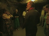 Tour group listening to tour guide inside dark room underground Stock Footage