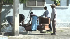 A victim of the Haiti earthquake is loaded into a coffin. - stock footage