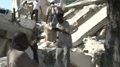 People remove bricks from a collapsed building during the Haiti earthquake. - stock footage