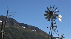 Windmill with mountains and blue sky - stock footage