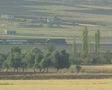 Train travelling through fields in distance - stock footage