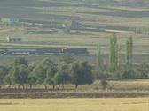 Train travelling through fields in distance Stock Footage