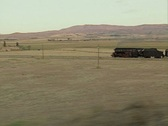 Moving view of steam train travelling through fields Stock Footage