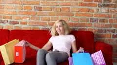 Attractive woman after shopping resting on sofa Stock Footage