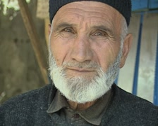 Close up of old man's face while sharpening knife - stock footage