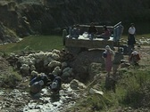 Workers washing fleeces in stream Stock Footage