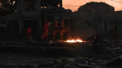 People walk around an open fire burning on the streets of haiti. Stock Footage