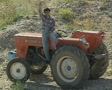 Man sitting on tractor and waving to camera Footage