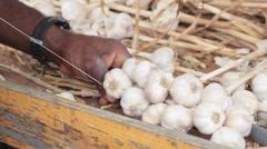 African American Man Braids Bulbs Of Garlic Stock Footage