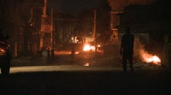 Stock Video Footage of Open fires burn in a rough neighborhood in a third world country.