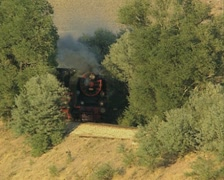 Moving black steam train and train whistle - stock footage