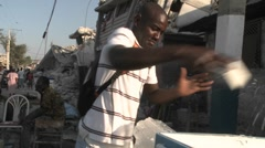 A man sells ice on the streets following the massive Haiti earthquake. - stock footage
