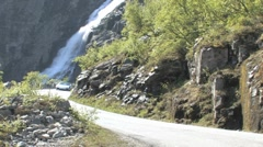 A Ferrari driving past a waterfall - stock footage