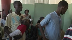 Haitians wait in a refugee center for news of victims of the Haiti earthquake. Stock Footage