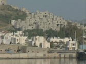 Zoom out from coastal buildings and passing boat to gulet Stock Footage