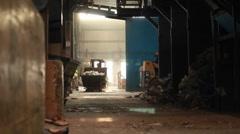 A skip loader picks up trash at a recycling center. - stock footage