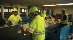 Workers sort trash at a recycling center. - stock footage