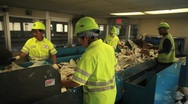 Stock Video Footage of Workers sort trash at a recycling center.