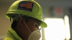 Stock Video Footage of An American factory worker wears a helmet with a flag.