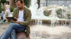 Young happy man with tablet computer sitting by the fountain, slow motion HD - stock footage