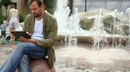 Stock Video Footage of Young happy man with tablet computer sitting by the fountain, slow motion HD