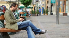 Young happy man with tablet computer sitting in the city HD - stock footage