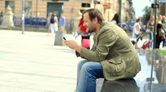 Happy young man sending sms, texting in the city HD Stock Footage